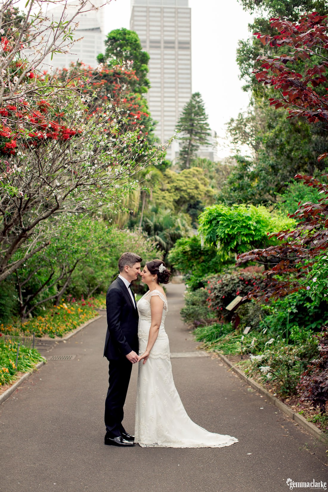 A bride and groom holding hands and standing nose to nose in a garden - Royal Botanic Gardens Wedding
