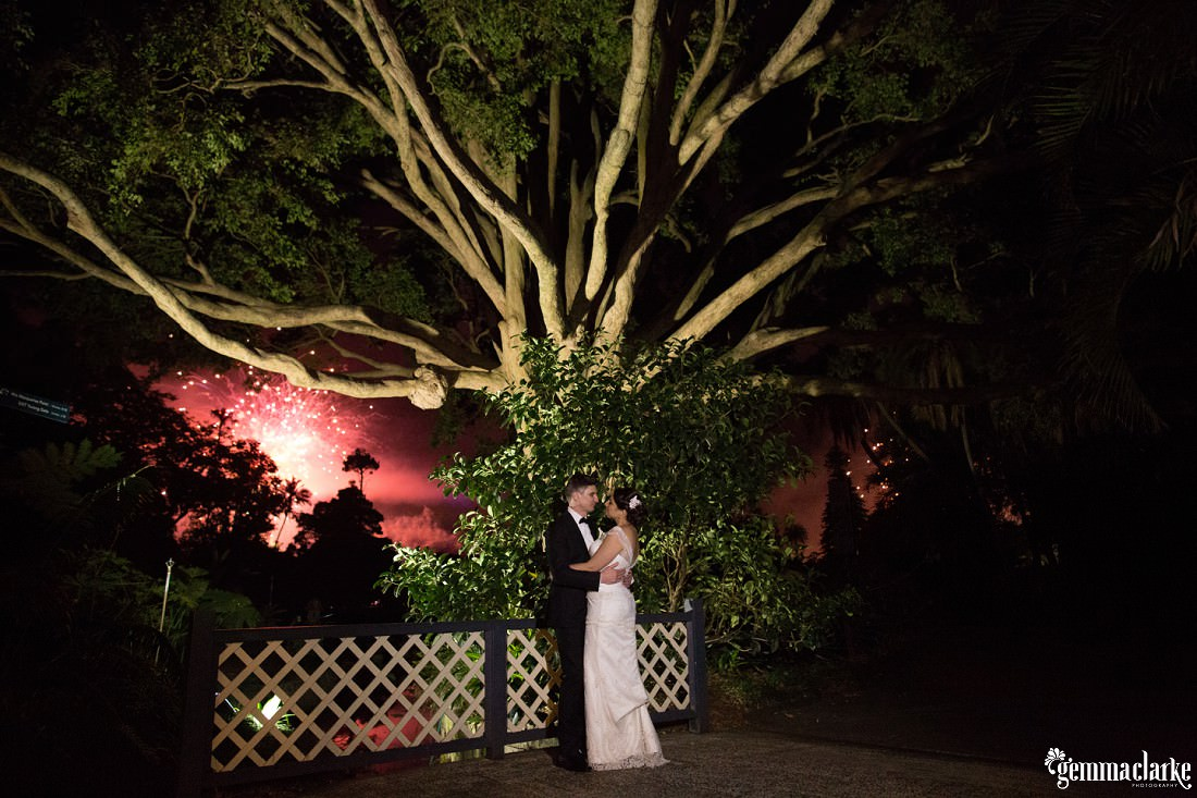 A bride and groom standing underneath a tree at night with fireworks going off in the background - Royal Botanic Gardens Wedding
