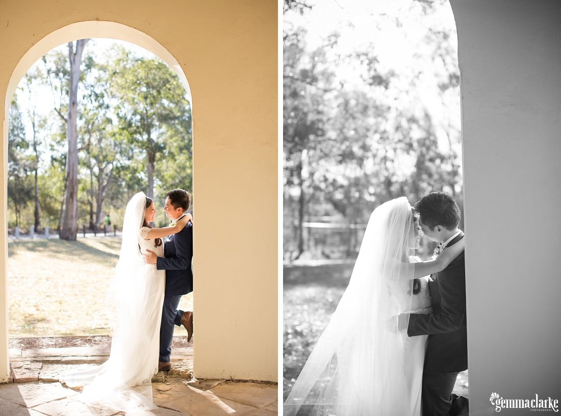 A bride and groom hold each other close while standing in an archway - Parramatta Wedding