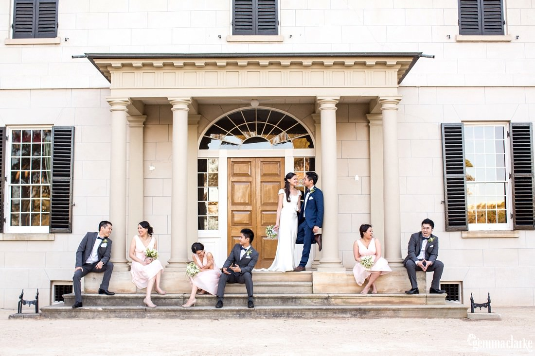 A bridal party relaxing around a doorway to a large building - Parramatta Wedding