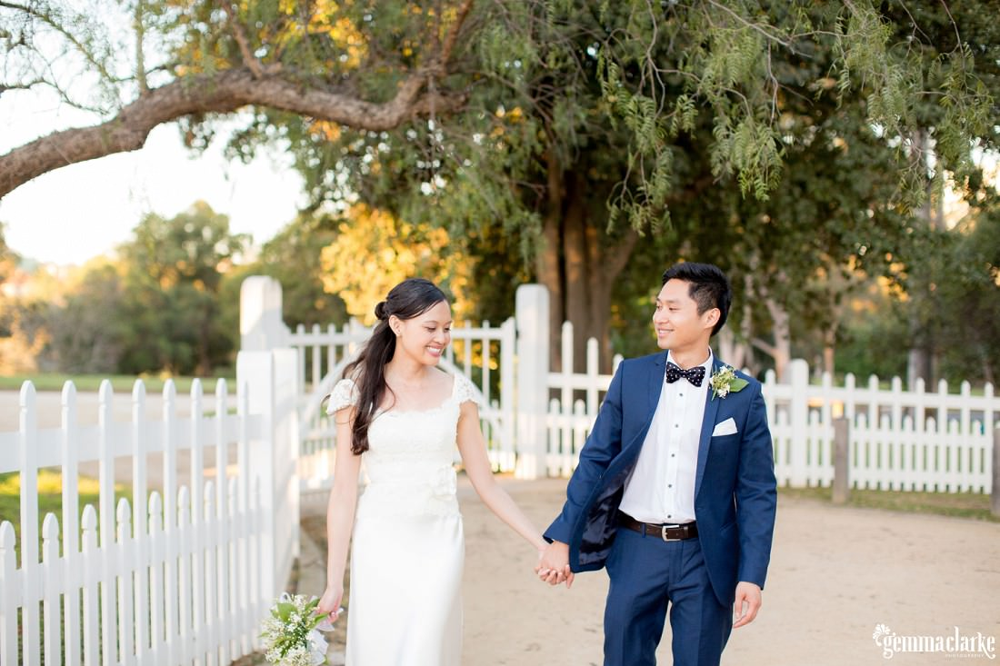 A smiling bride and groom hold hands while walking down a dirt parth by a white picket fence - Parramatta Wedding