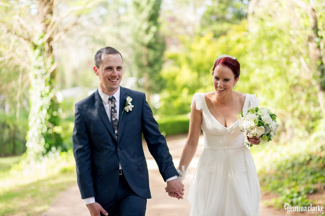 A smiling bride and groom walking hand and hand through a garden - Biota Dining Wedding