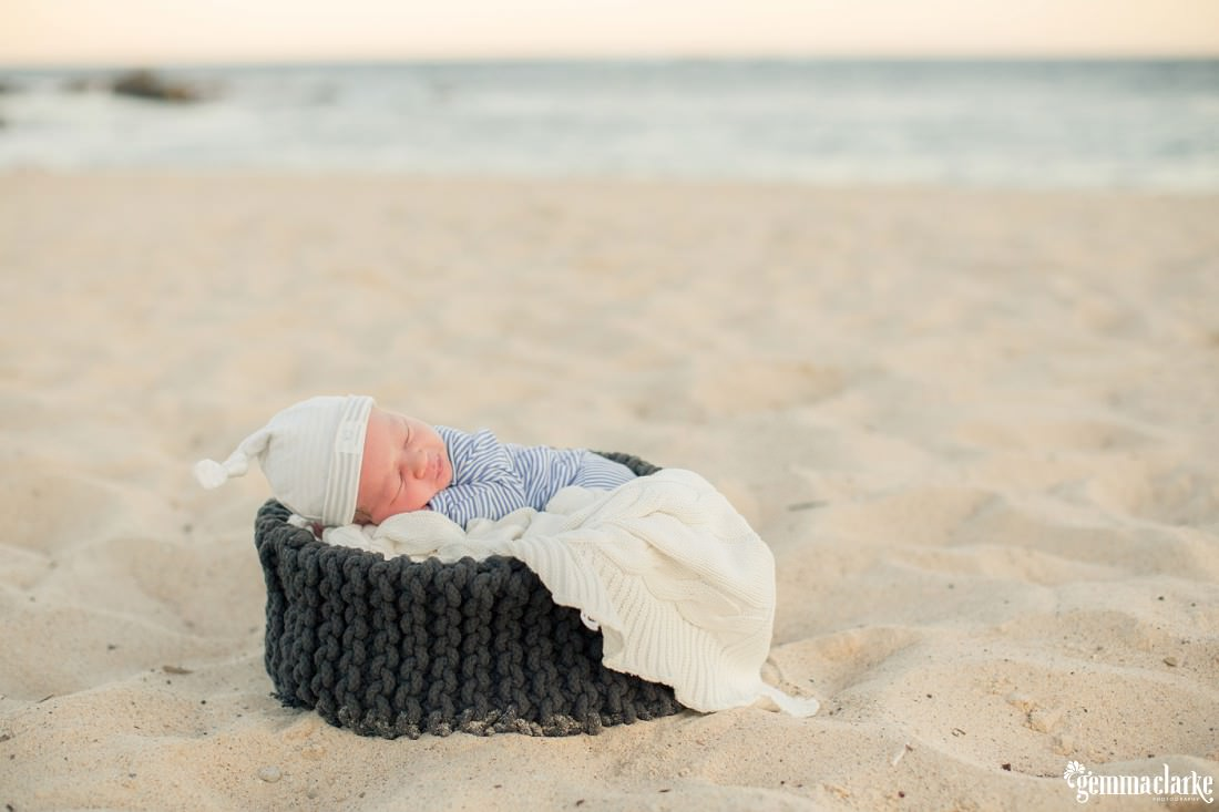 A baby sleeping in a basket on the beach – Newborn Lifestyle Portraits