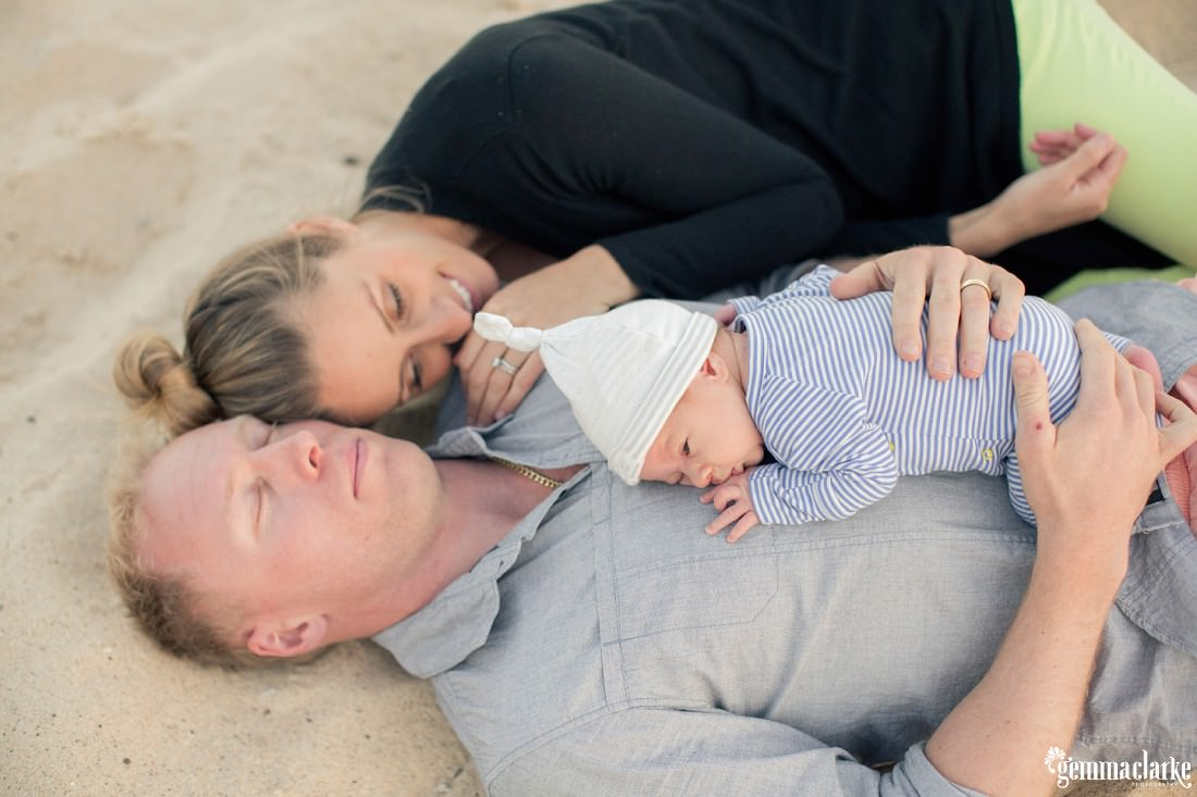 A young mother and father laying on a beach with their newborn son – Newborn Lifestyle Portraits