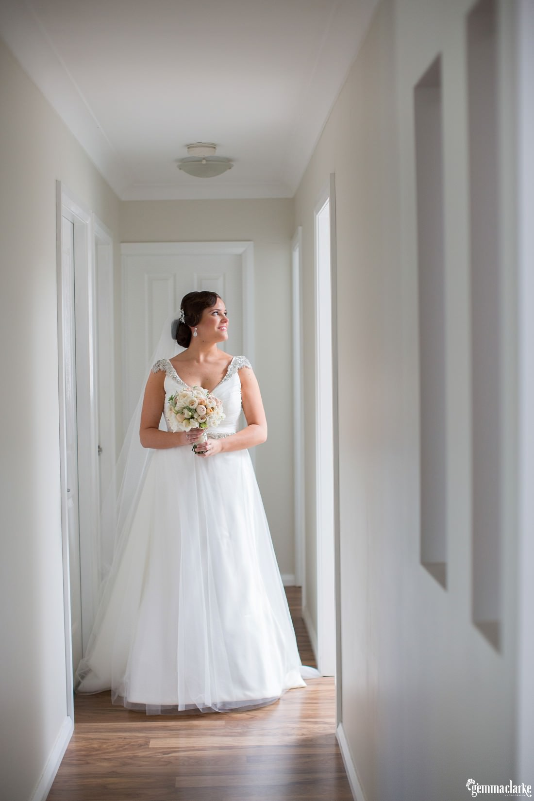 A bride standing in a hallway with light shining on her through a doorway - Western Sydney Wedding