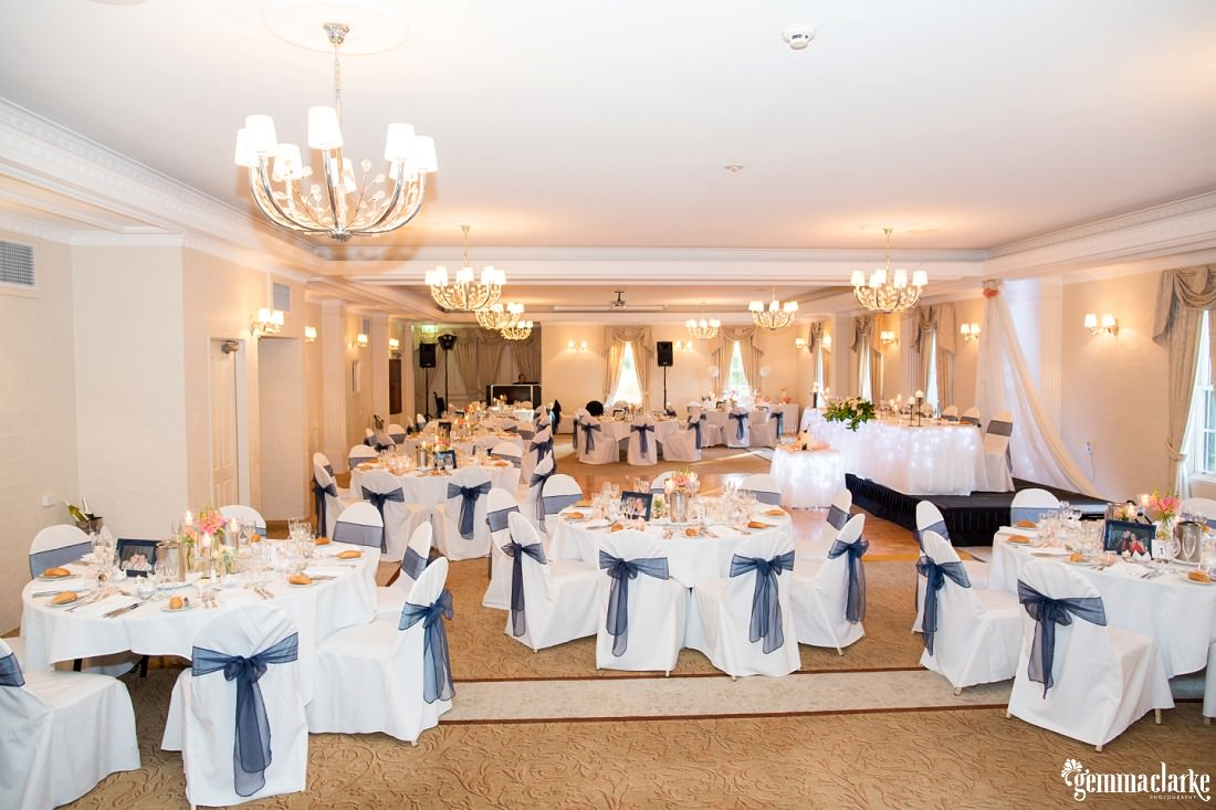 Reception setup with white tableclotchs and chair covers with blue bows - Western Sydney Wedding