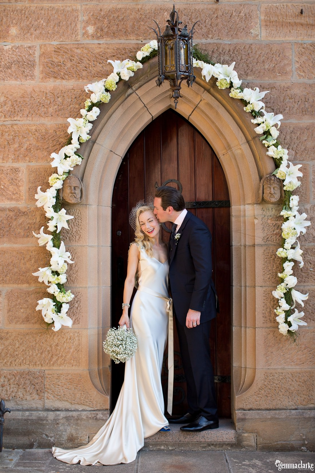 A groom kisses his smiling bride on the forehead as they stand by an arched church door lined with white flowers - Eastern Suburbs Wedding