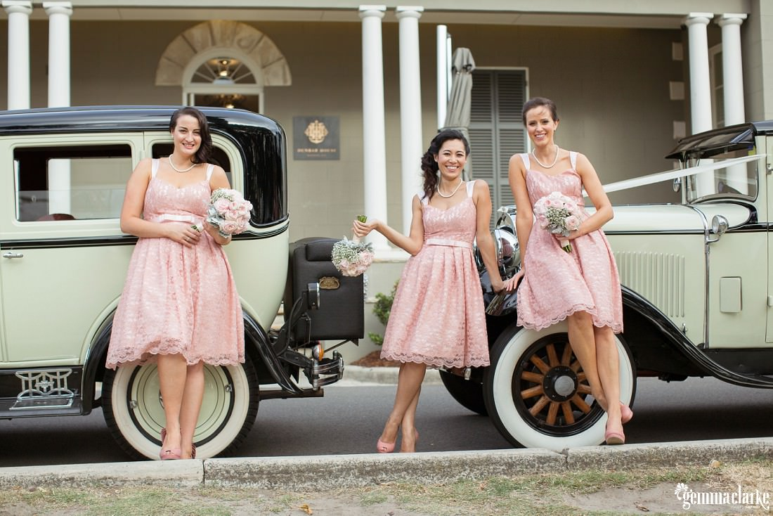 Bridesmaids in pink dresses posing with vintage wedding cars - Eastern Suburbs Wedding