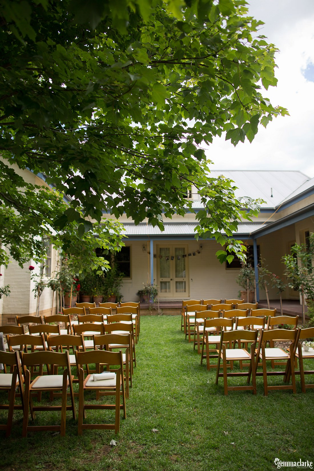 Ceremony setup at this Backyard Wedding overlooking the cottage style house with wooden chairs and a big overhanging tree