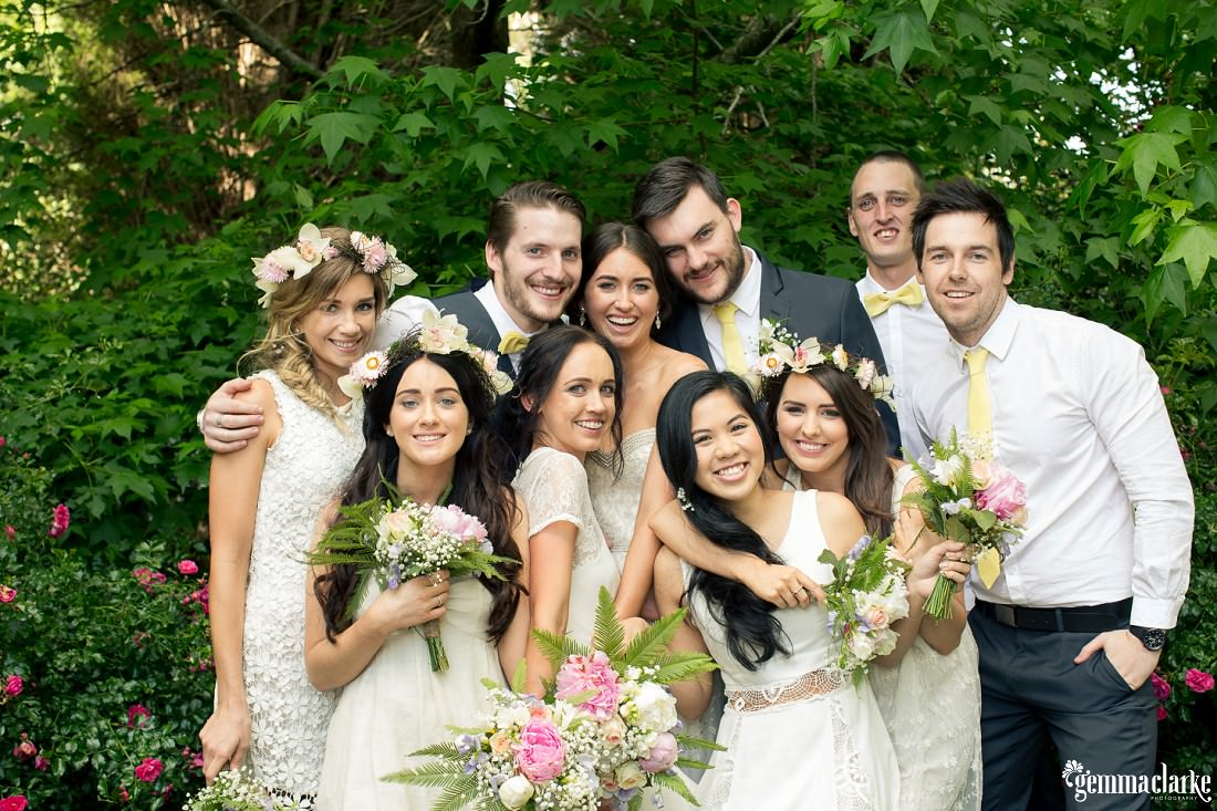 A bridal party posing together in front of lovely greenery in a backyard garden - Backyard Wedding