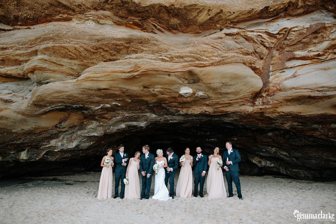Bridal party underneath large caves beach cave opening and all looking at each and laughing at this Lake Macquarie Wedding