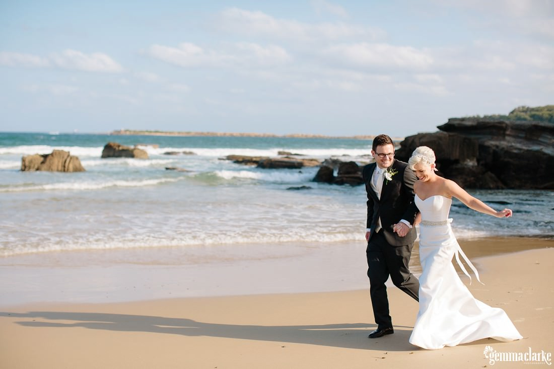 A bride and groom walk hand-in-hand along Caves Beach - Lake Macquarie Wedding