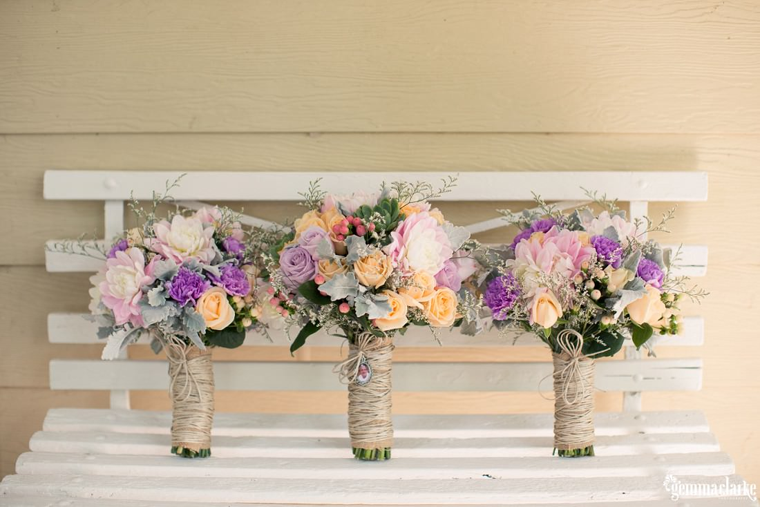 Lightly pastel coloured bouquets on a white bench seat - Merribee Wedding
