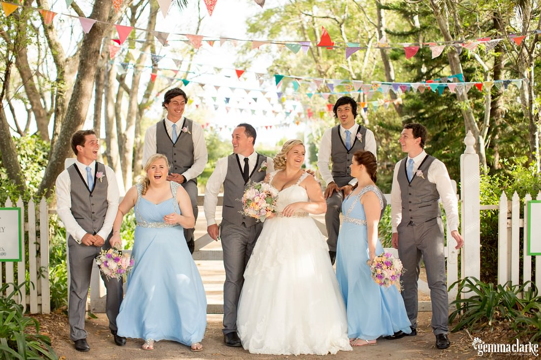 A bridal party posing on a white wooden gate amongst trees and under colourful bunting - Merribee Wedding