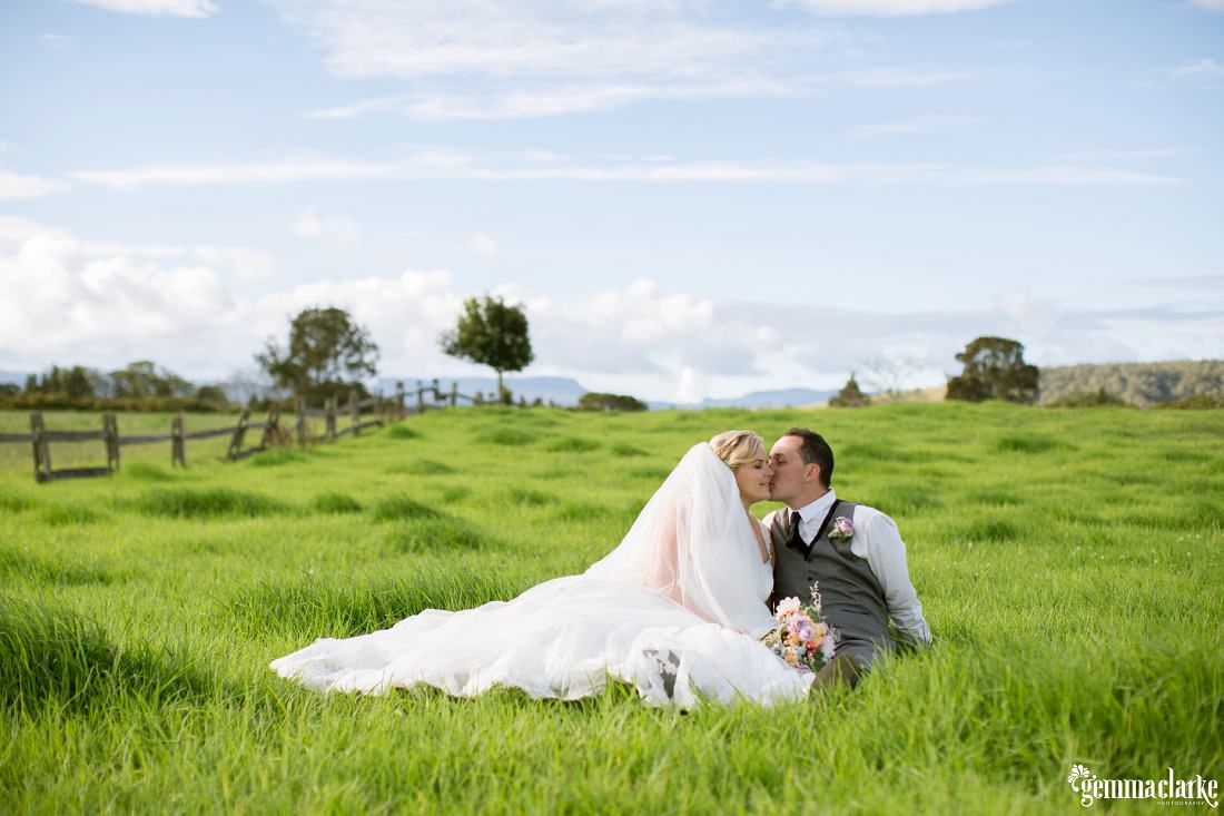 A bride and groom sitting amongst the long grass in a meadow - Merribee Wedding