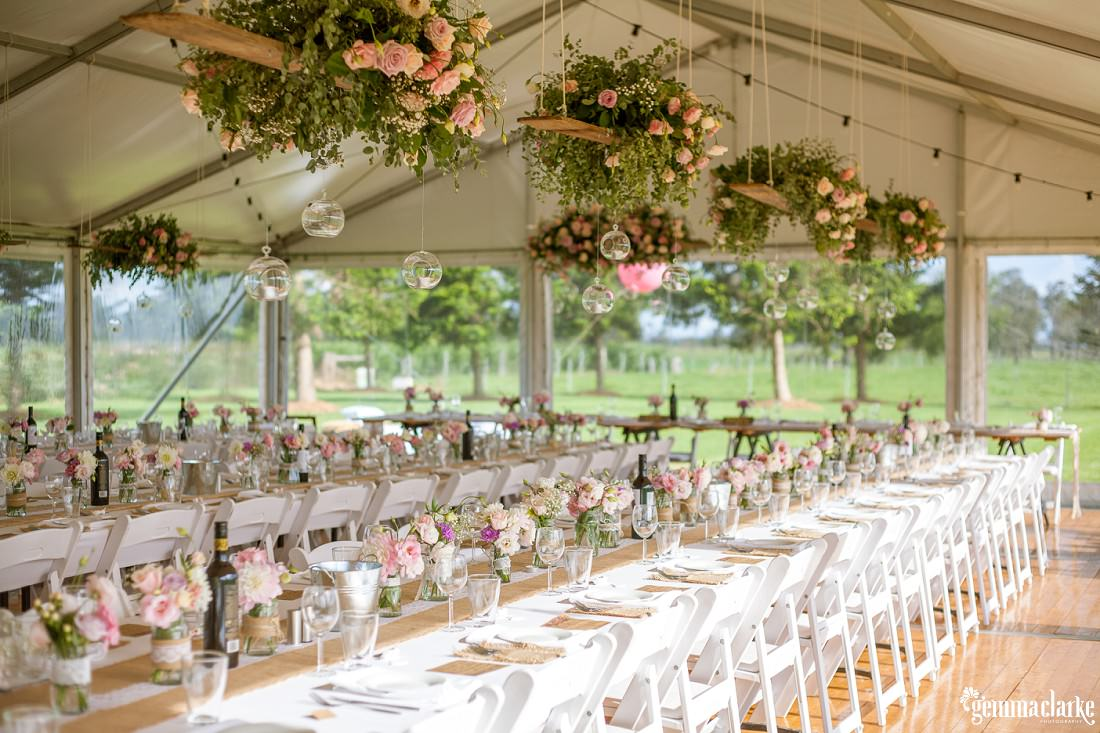 Stunning set up of the reception room with flowers hanging from planks of wood and also candles. Stunning pastel colours at this Merribee Wedding