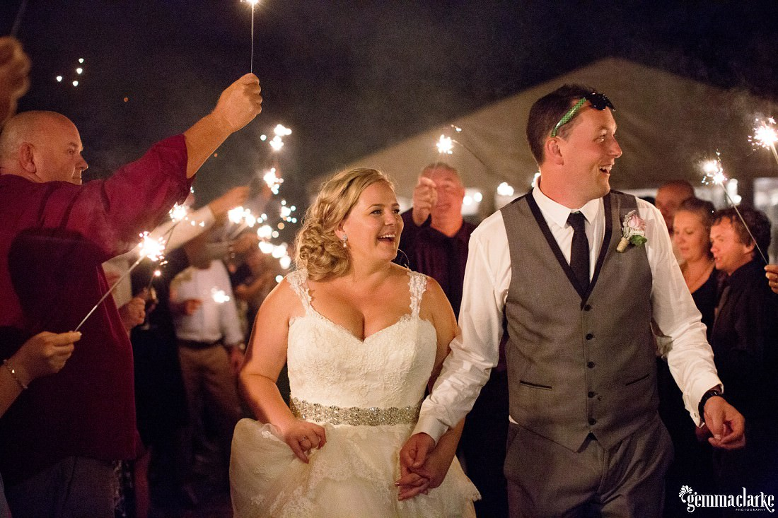 Wedding guests seeing off the happy couple with sparklers at the end of their Merribee Wedding