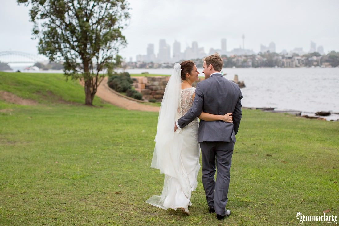A bride and groom walk arm in arm by the water with the Sydney skyline in the background - Hunter's Hill Wedding