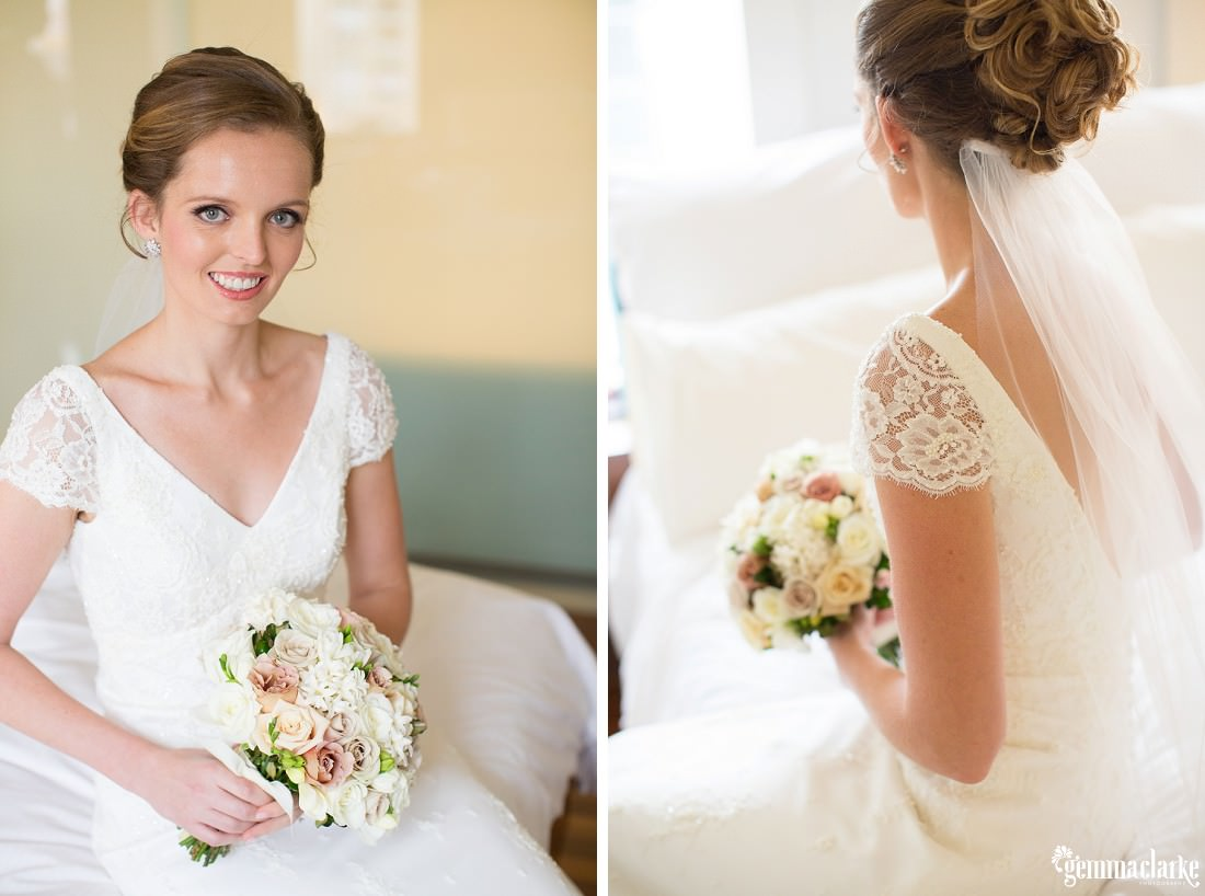 A bride sitting on a bed in her white bridal gown with lacey sleeves and pretty lightly coloured bouquet - Gunners Barracks Wedding