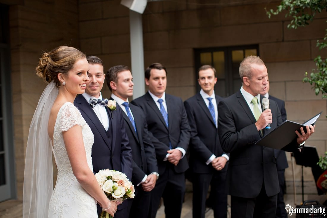 The bride looking away during the ceremony as the groom gazes at her and the celebrant and 2 of the three groomsmen look elsewhere. The 3rd groomsman is looking at the groom and smiling. A wonderful moment at this Gunners Barracks Wedding.