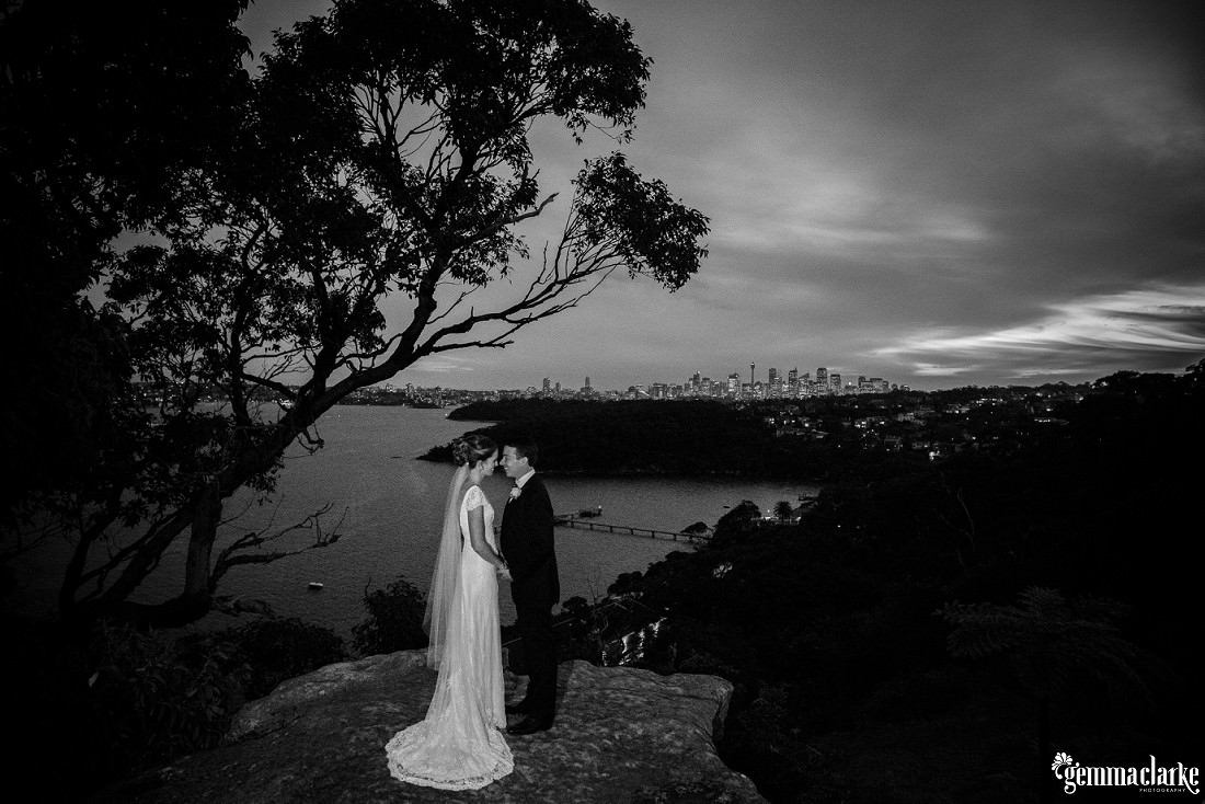 A bride and groom standing close on a rock with Sydney Harbour and the Sydney skyline in the background - Gunners Barracks Wedding