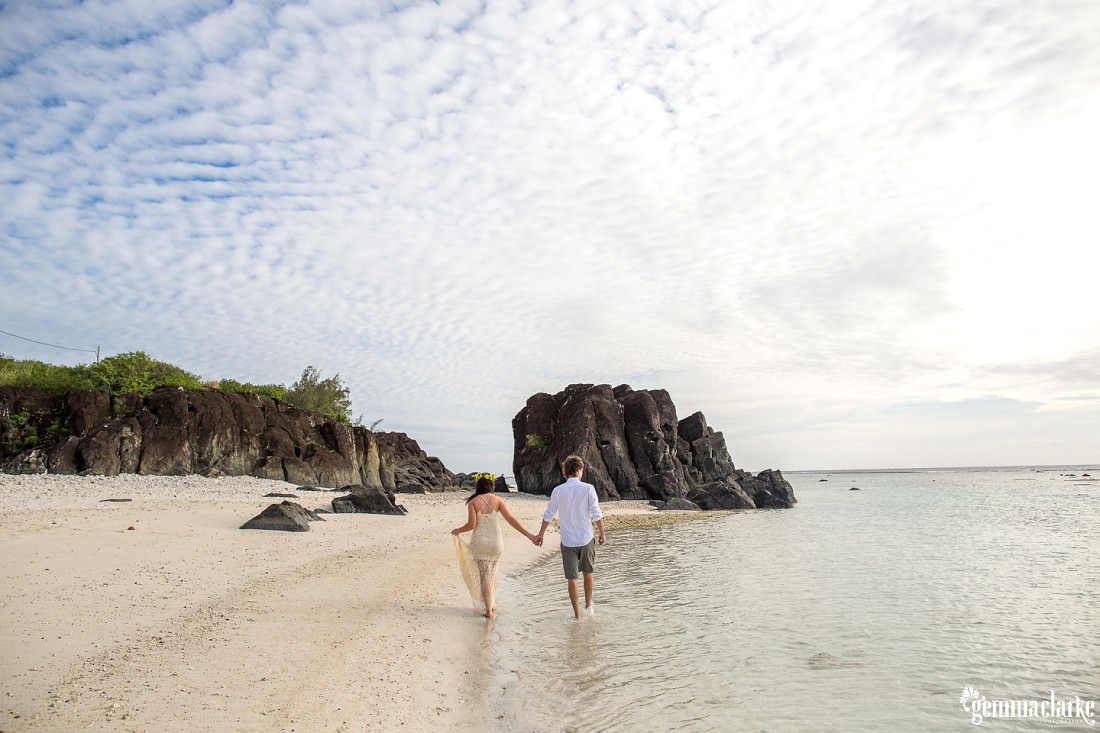A man and woman walking hand in hand in the shallow water at the beach - Sunset Portraits in Paradise