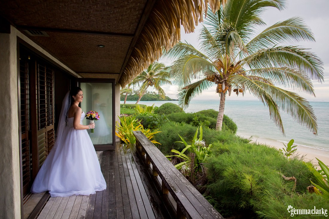 A bride on a balcony overlooking a tropical beach - South Pacific Wedding
