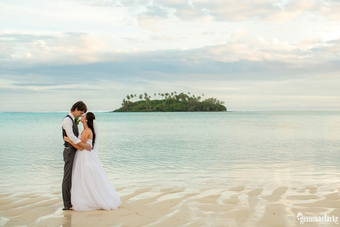 Bride and Groom embracing each other on the beach with the clear waters and a little island in the background, South Pacific Wedding