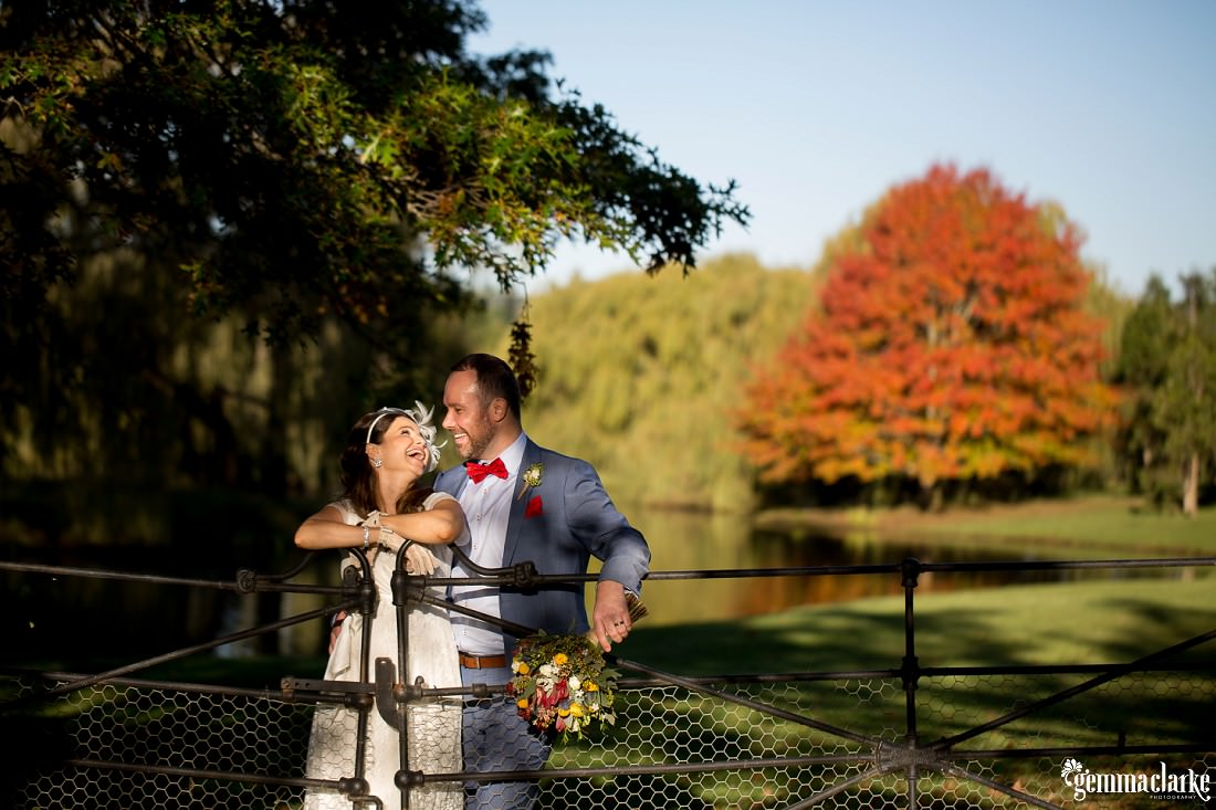 Bride and Groom laughing and looking at each other as they hang over an iron gate with the lake and a bright red tree in the background at this Autumn Southern Highlands Wedding