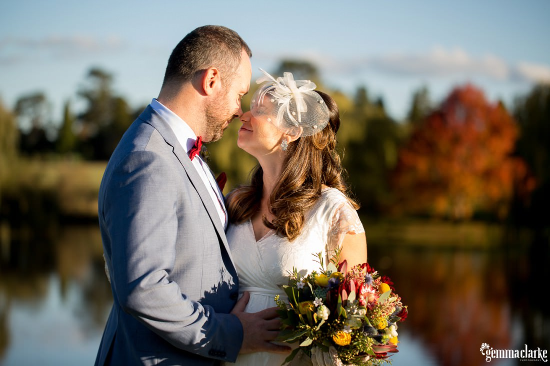 A bride and groom standing near a small lake pressing their noses together - Autumn Southern Highlands Wedding