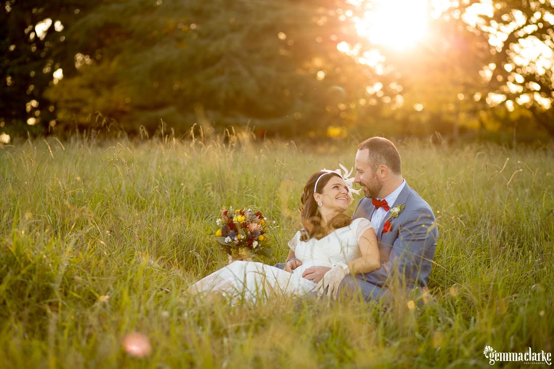 A bride and groom sitting together in a field of long grass - Autumn Southern Highlands Wedding