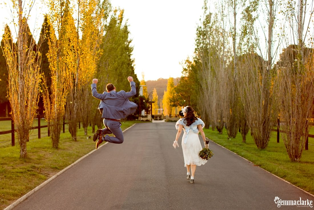 Bride and groom walking down road lined with trees and the groom has jumped in the air with his hands held high - he looks very excited at this Autumn Southern Highlands Wedding