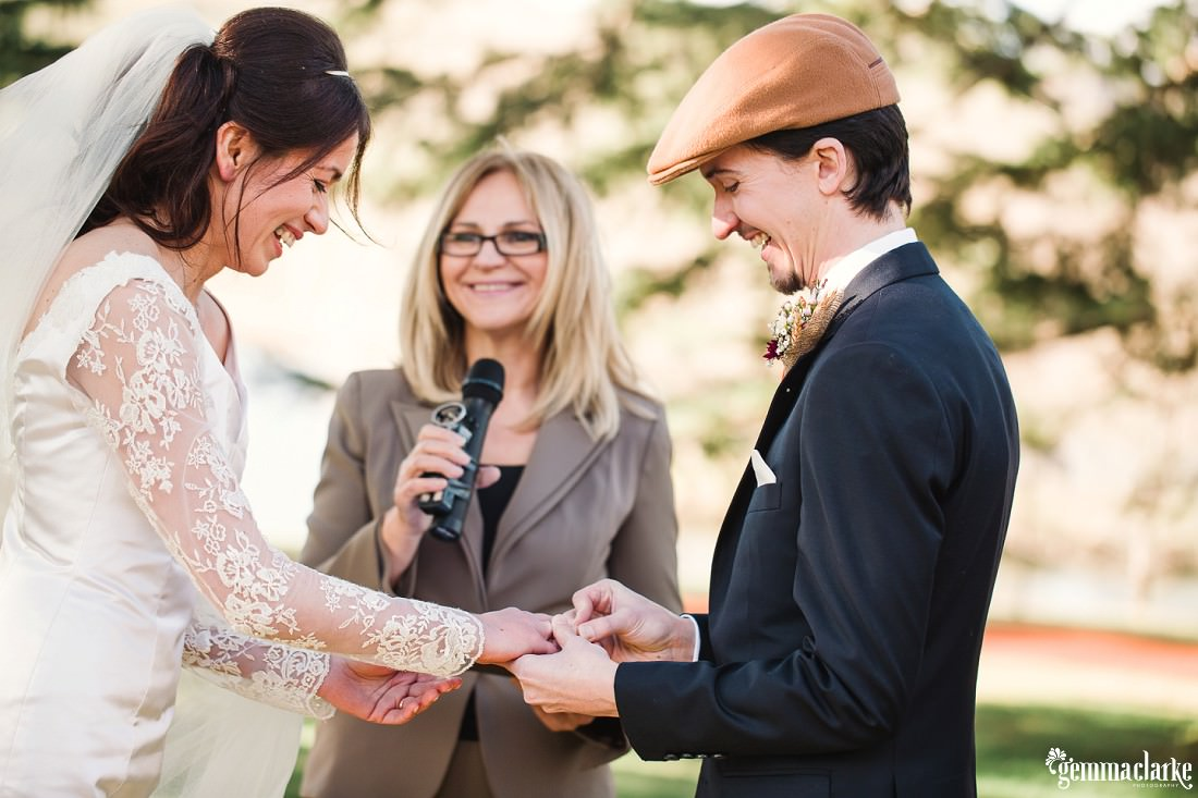 All smiles as a groom puts a ring on his bride's finger - Southern Highlands Winter Wedding