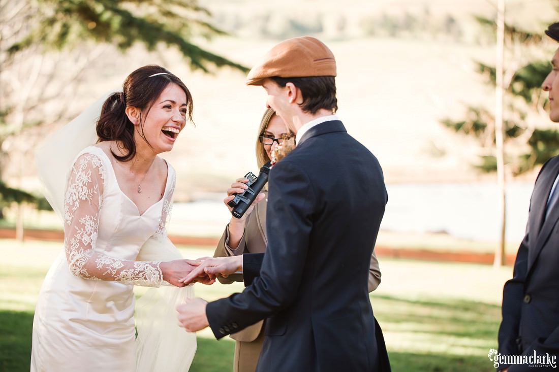 Big smiles as a groom puts a ring on his bride's finger - Southern Highlands Winter Wedding