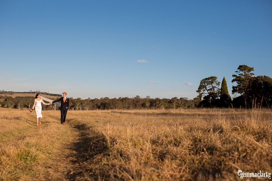 A bride and groom holding hands walking through a grassy field - Southern Highlands Winter Wedding