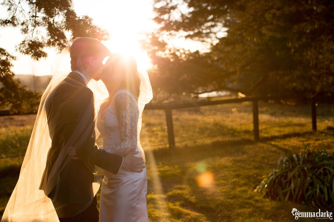 A bride and groom share a kiss under her veil as they are bathed in streaming sunlight - Southern Highlands Winter Wedding