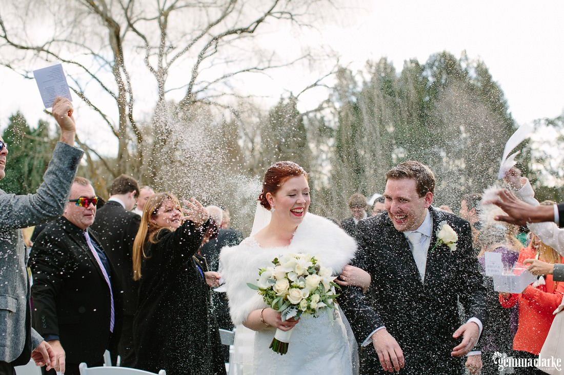 "A bride and groom being showered with ""snow"" confetti after their wedding ceremony - Bowral Winter Wedding"