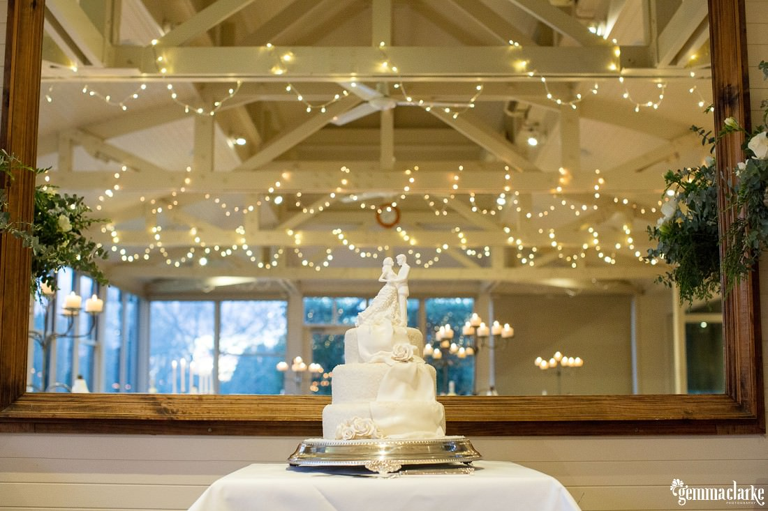 Three tier traditional white wedding cake with bride and groom topper under fairy lights - Bowral Winter Wedding