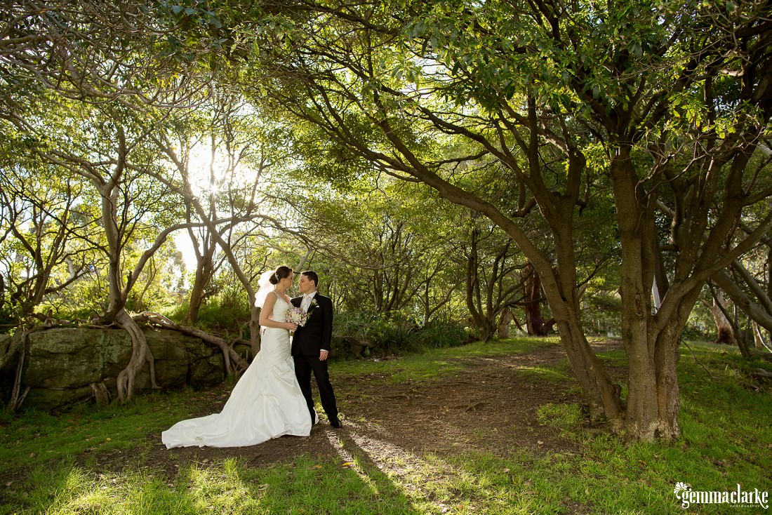 A bride and groom standing together amongst trees with sun streaming in from behind - Woolwich Wedding