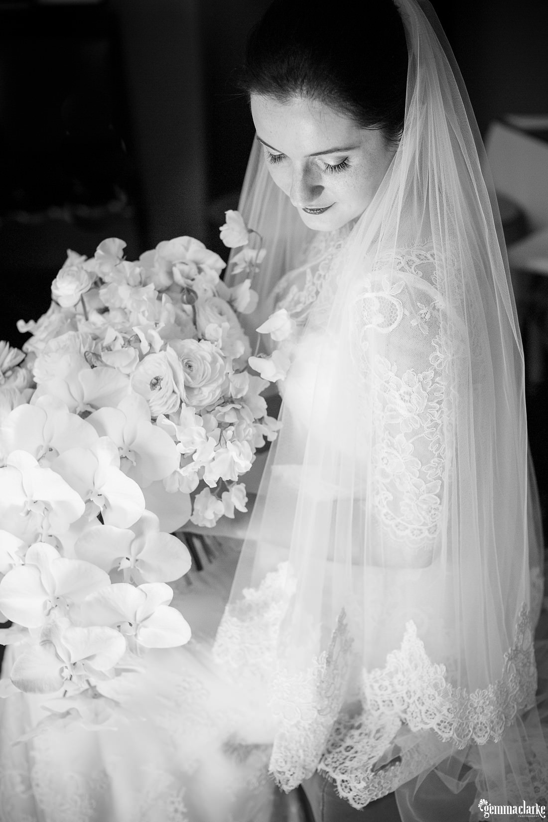 A bride posing with her large bouquet, looking down over her shoulder - Vaucluse House Wedding