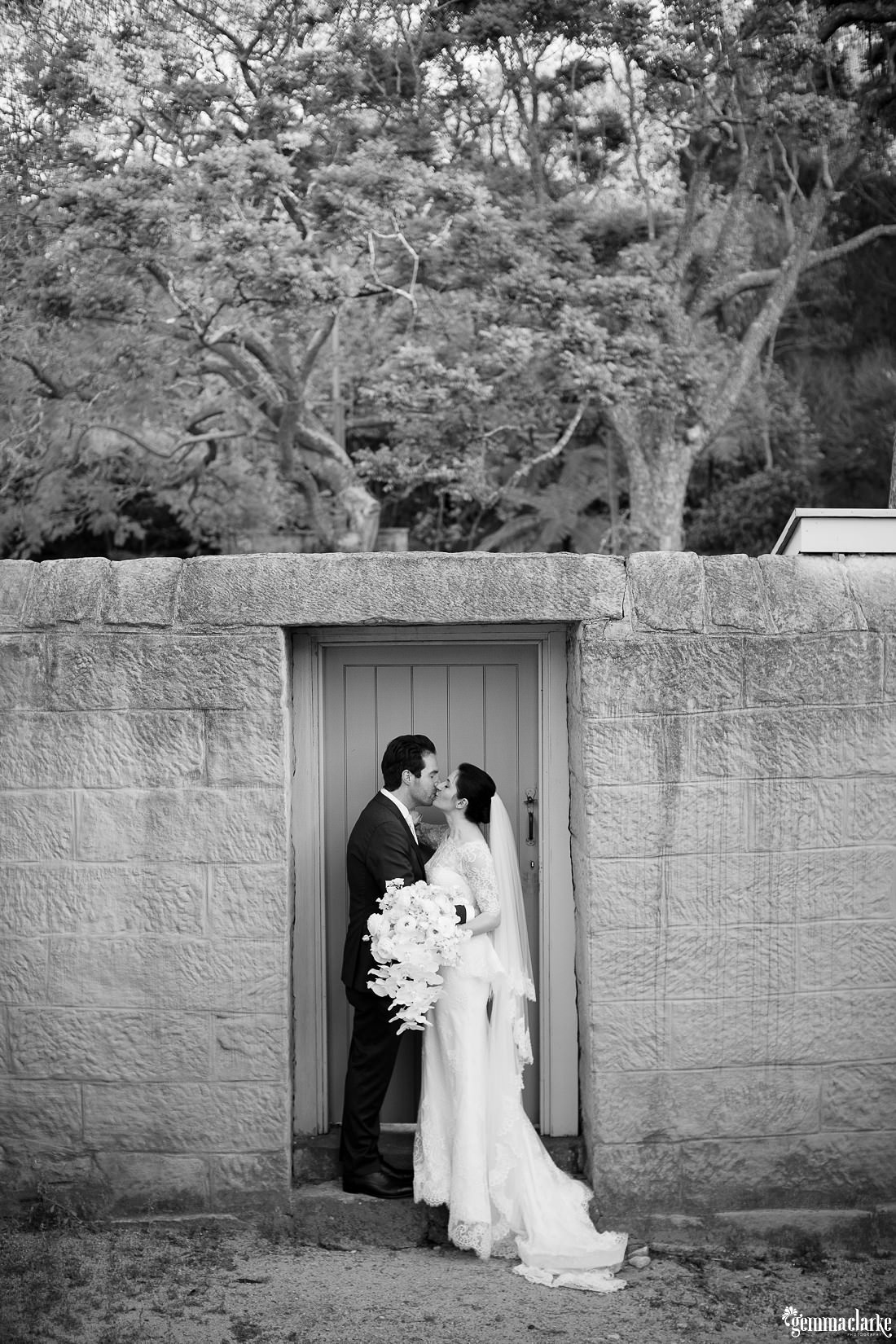 A bride and groom kiss while standing on a doorstep of a wooden doorway in a stone wall - Vaucluse House Wedding