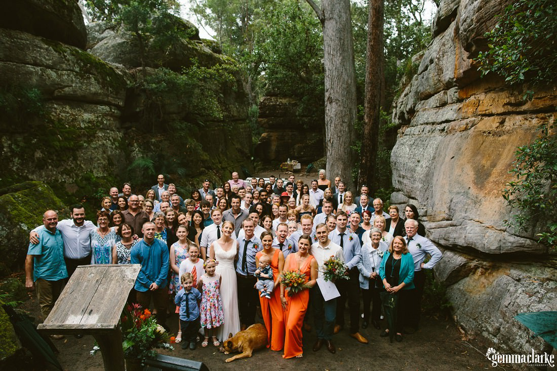 A bride and groom and all their wedding guests gathered at an open air cathedral amongst large rock formations – Kangaroo Valley Bush Retreat