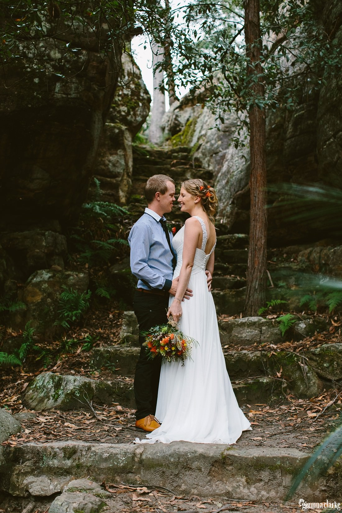A bride and groom leaning in close to each other in front of rock stairs – Kangaroo Valley Bush Retreat