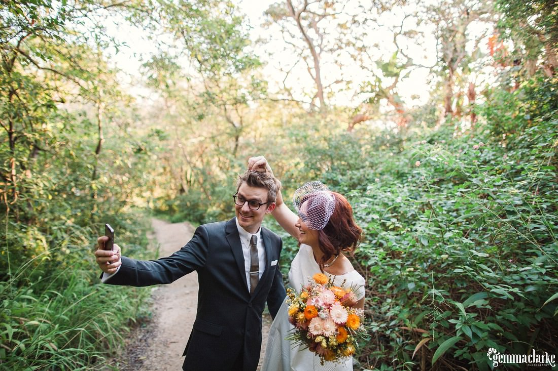 Fun Sydney Wedding Portrait of the bride and groom taking a selfie with the bride holding up the groom's hair at the front. They are on a bush path.