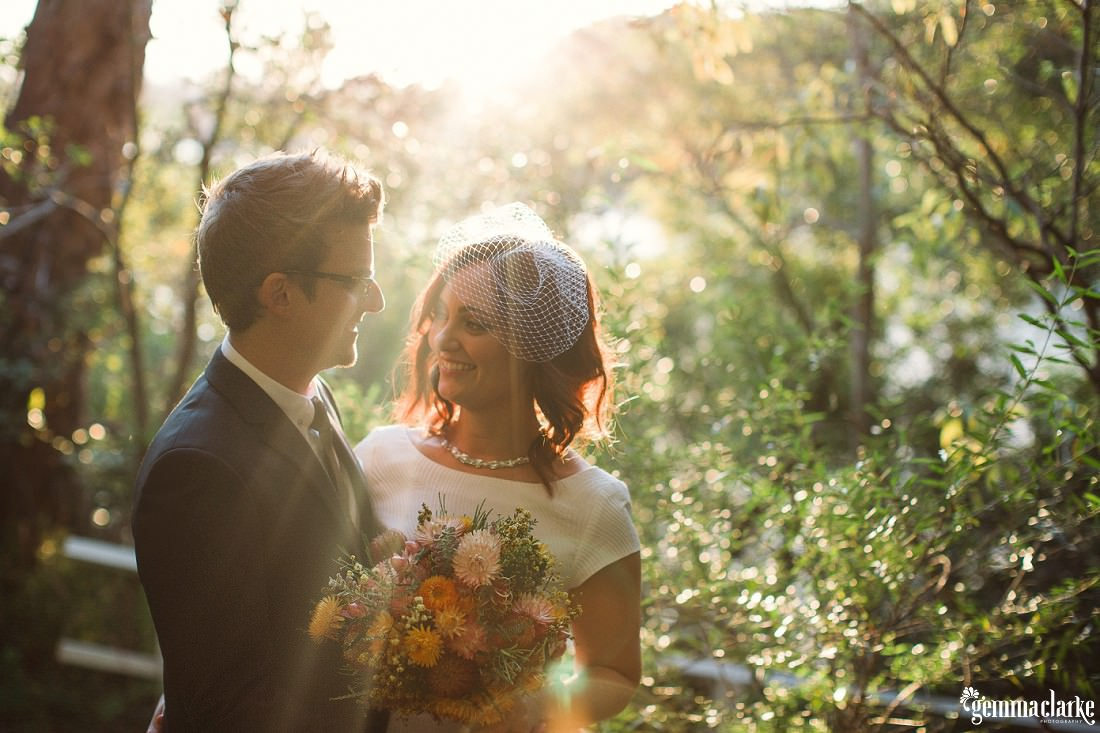 A bride and groom stand close and look at each other lovingly as sun streams in from behind - Fun Sydney Wedding