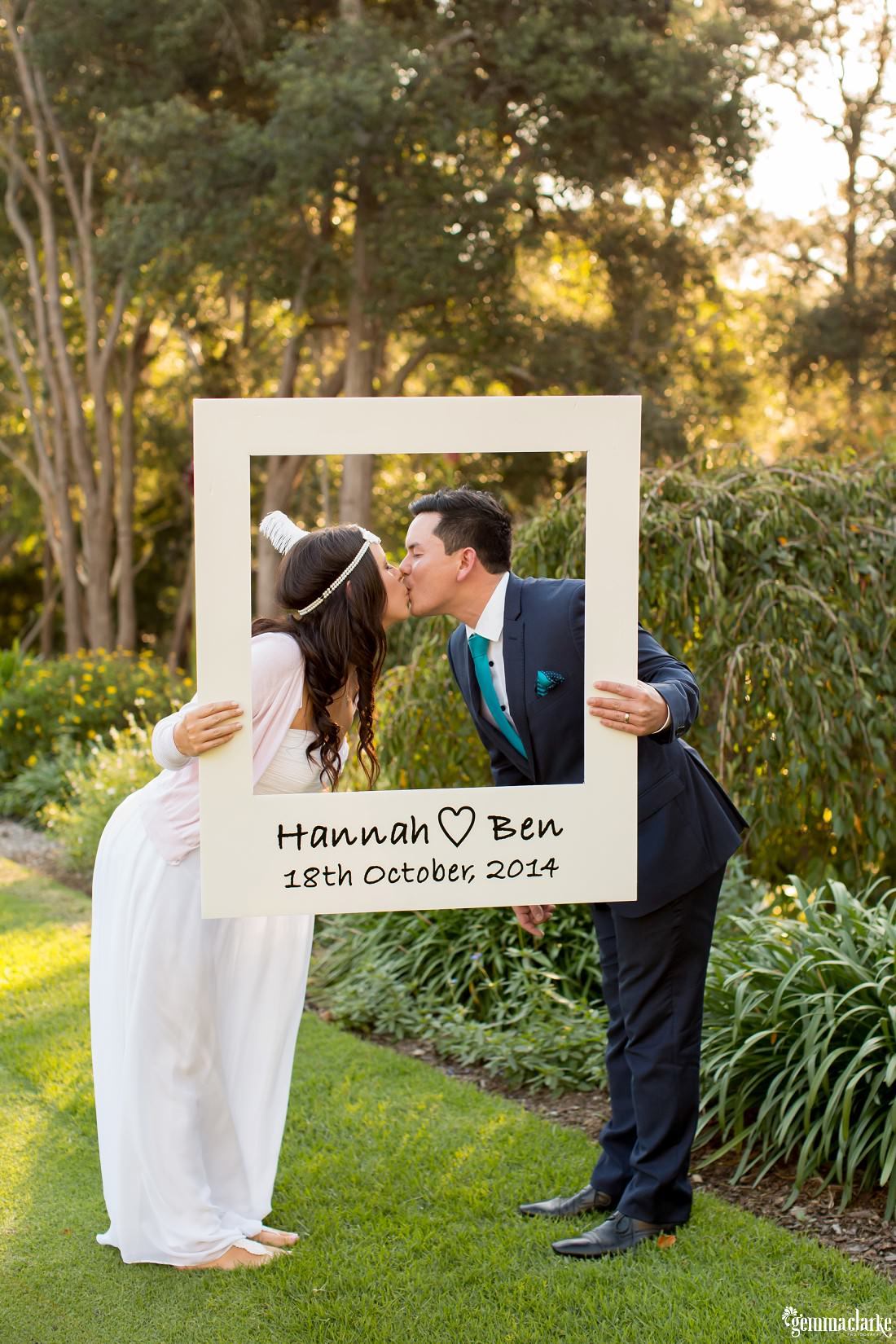 "A bride and groom leaning in to kiss while holding up a ""photo frame"" - Pennant Hills Golf Club Wedding"