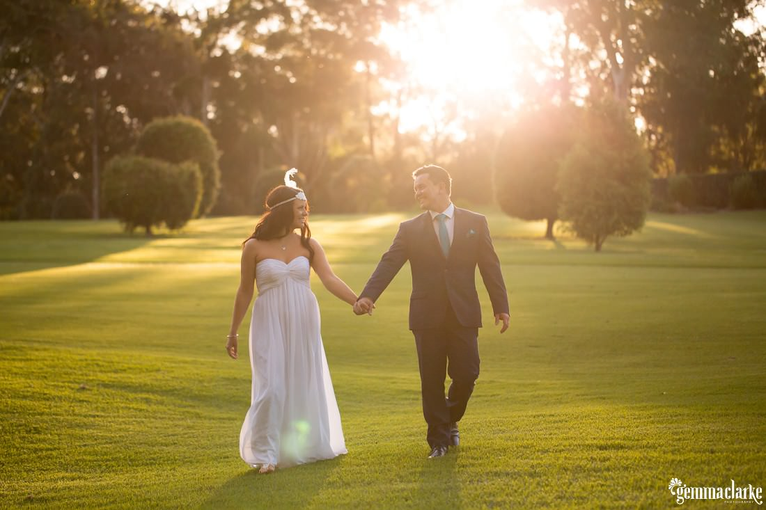 A bride and groom walking hand in hand across a golf course with sunlight streaming in through trees from behind - Pennant Hills Golf Club Wedding