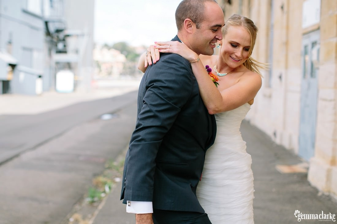 A bride with her arms around her groom - The Theatre Bar at the End of the Wharf Wedding