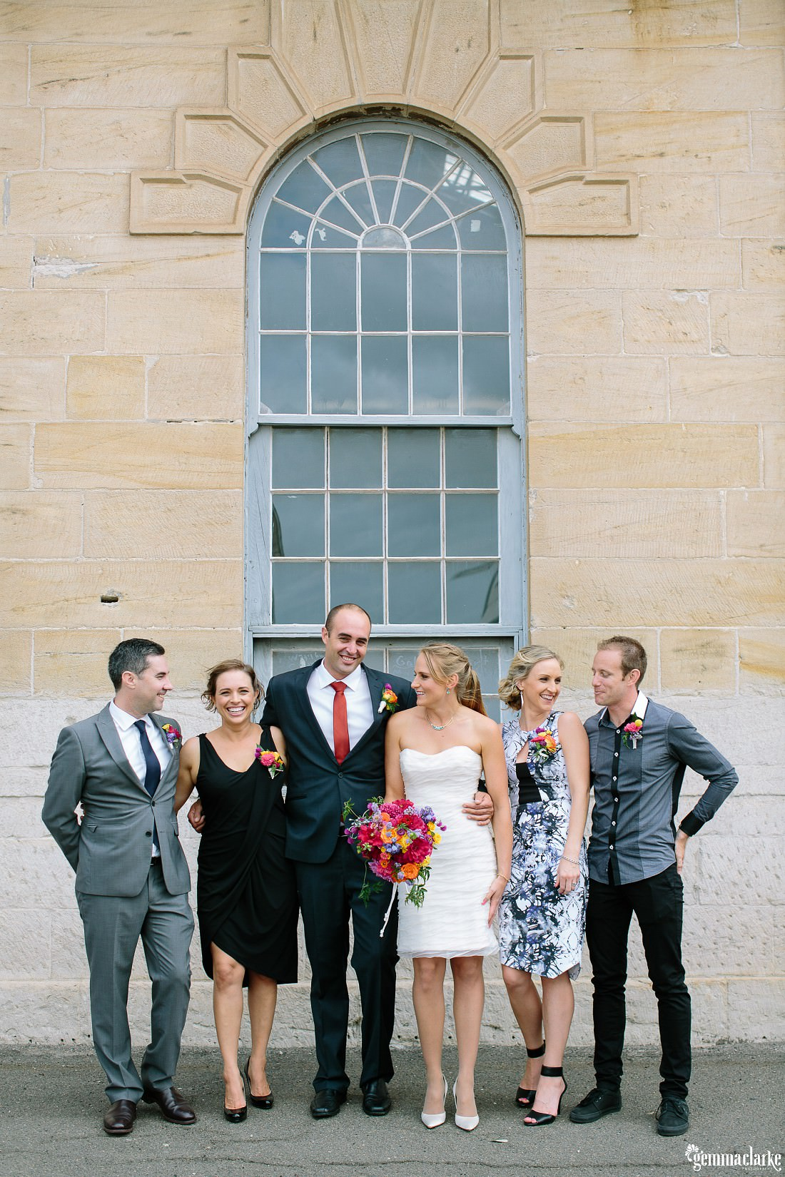 A wedding party standing together in front of a sandstone building - The Theatre Bar at the End of the Wharf Wedding