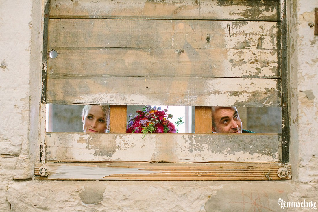 A bride and groom peaking through an opening in a slatted window - The Theatre Bar at the End of the Wharf Wedding